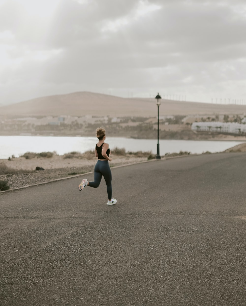 woman in black tank top and white pants running on gray asphalt road during daytime