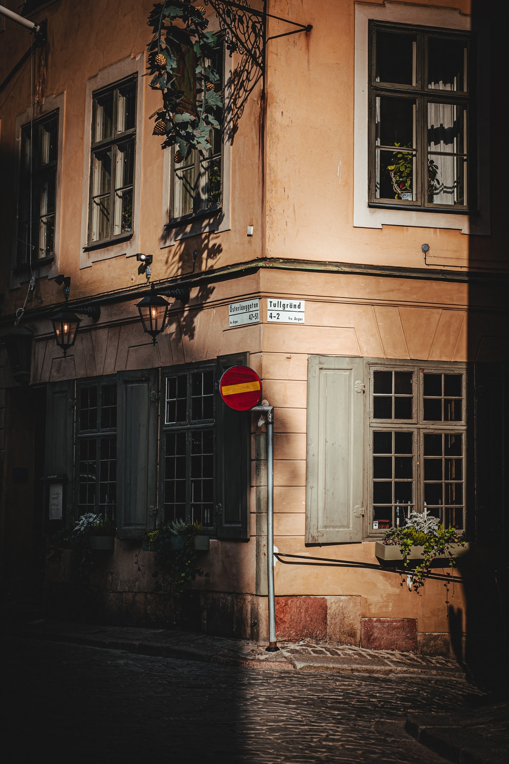 red and black outdoor lantern on brown concrete building