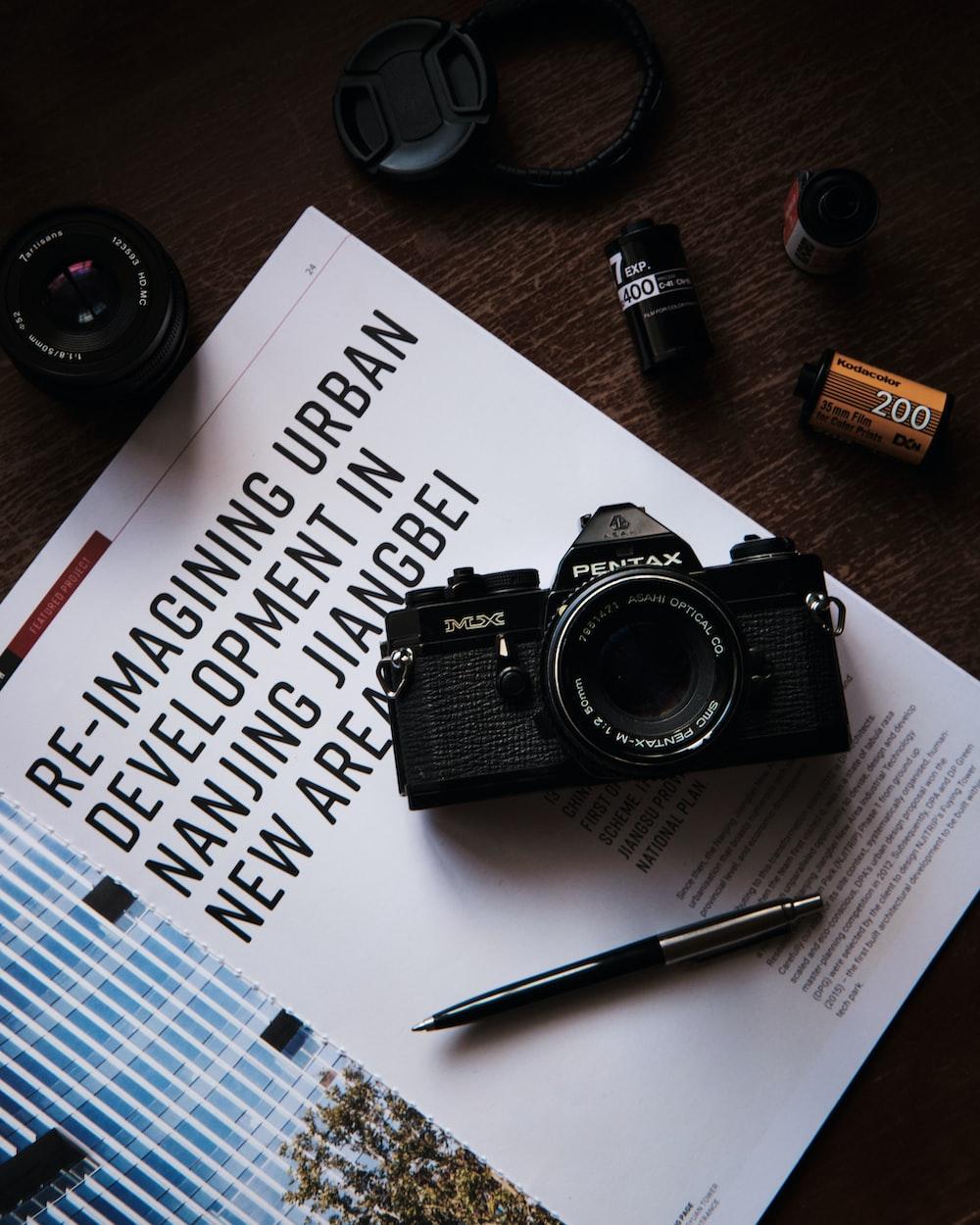 black nikon dslr camera beside brown and black click pen on white printer paper