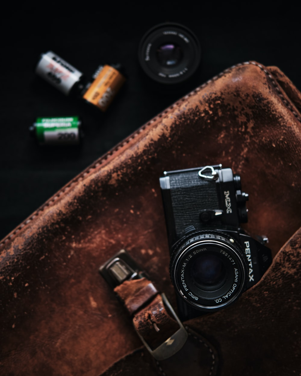 black and silver camera on brown leather textile