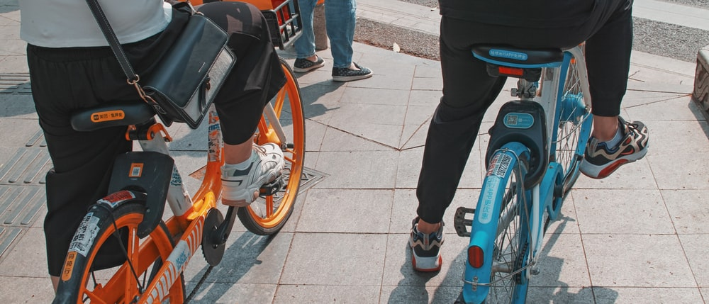 person in black pants and black shoes standing beside orange motorcycle