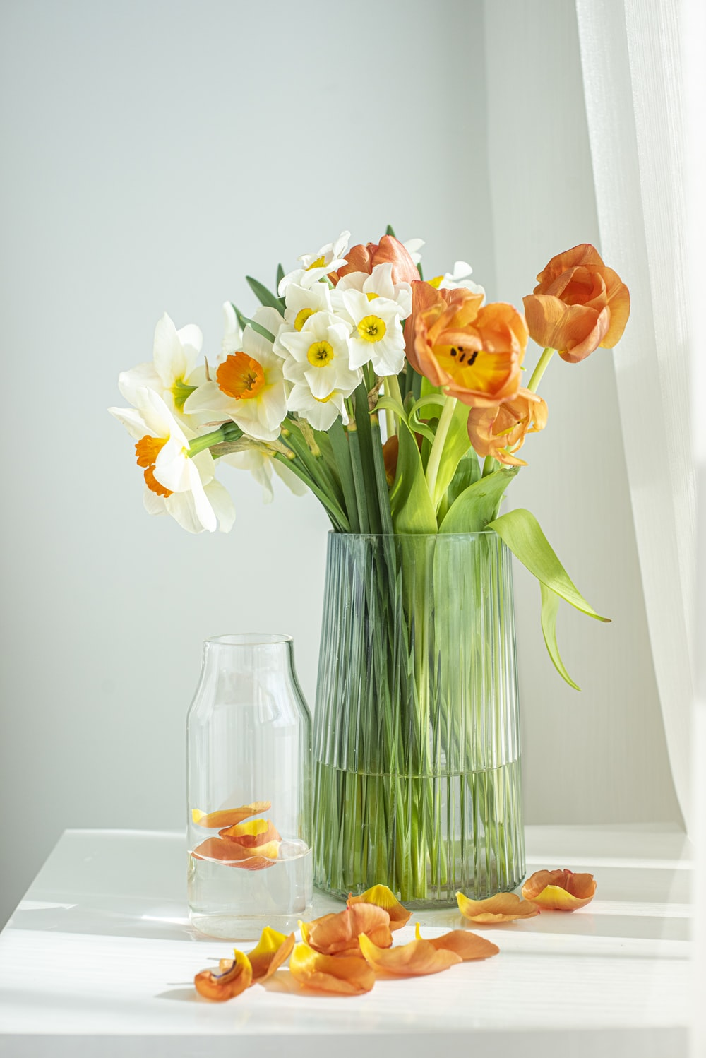 orange and yellow flowers in clear glass vase