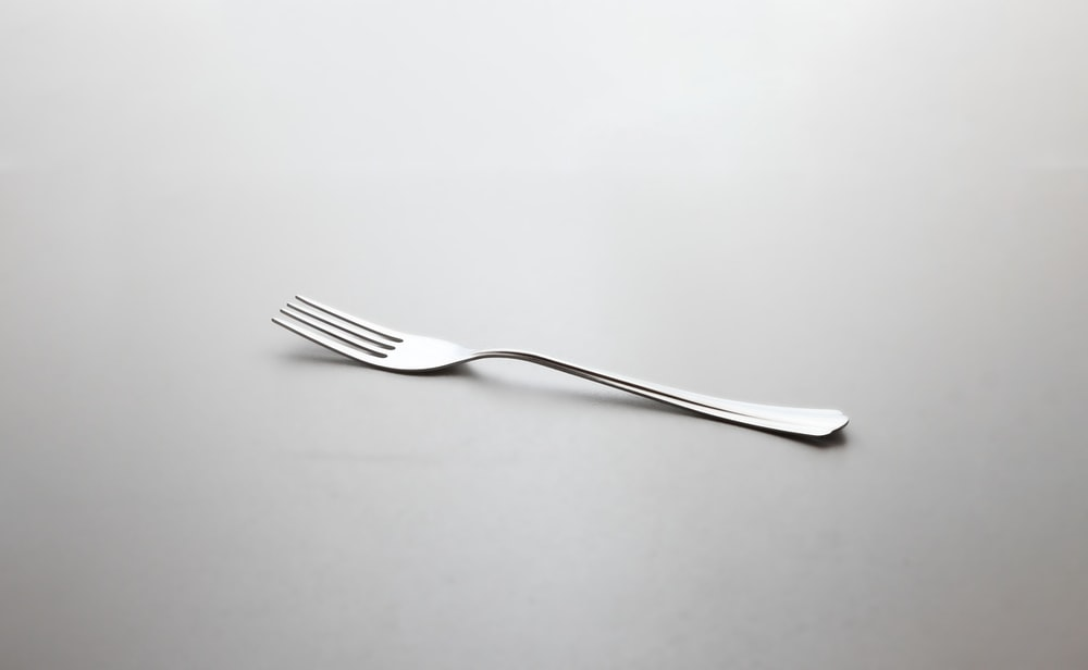 silver fork on white surface
