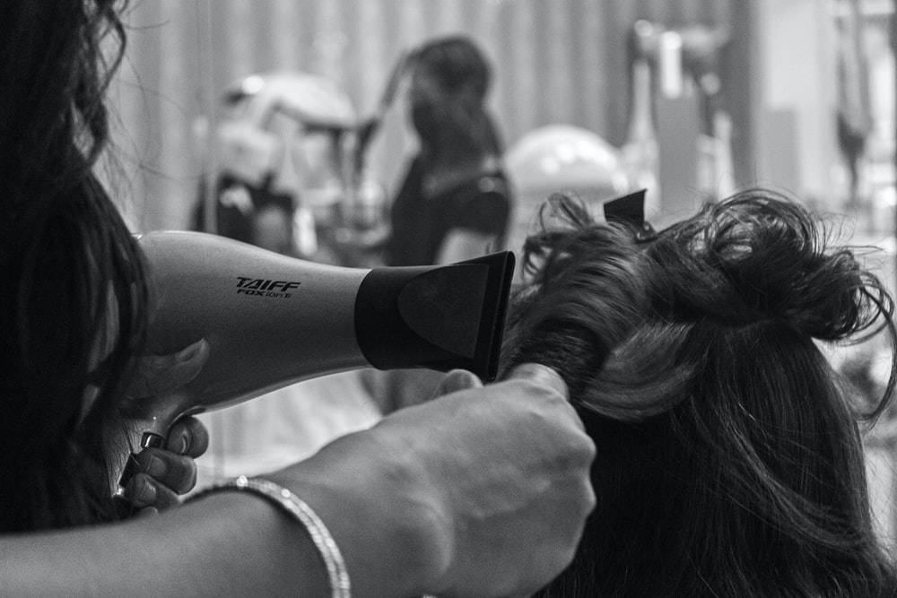 grayscale photo of woman holding hair blower