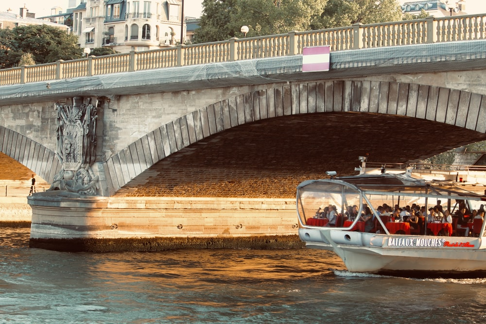 white and brown boat on water under bridge during daytime