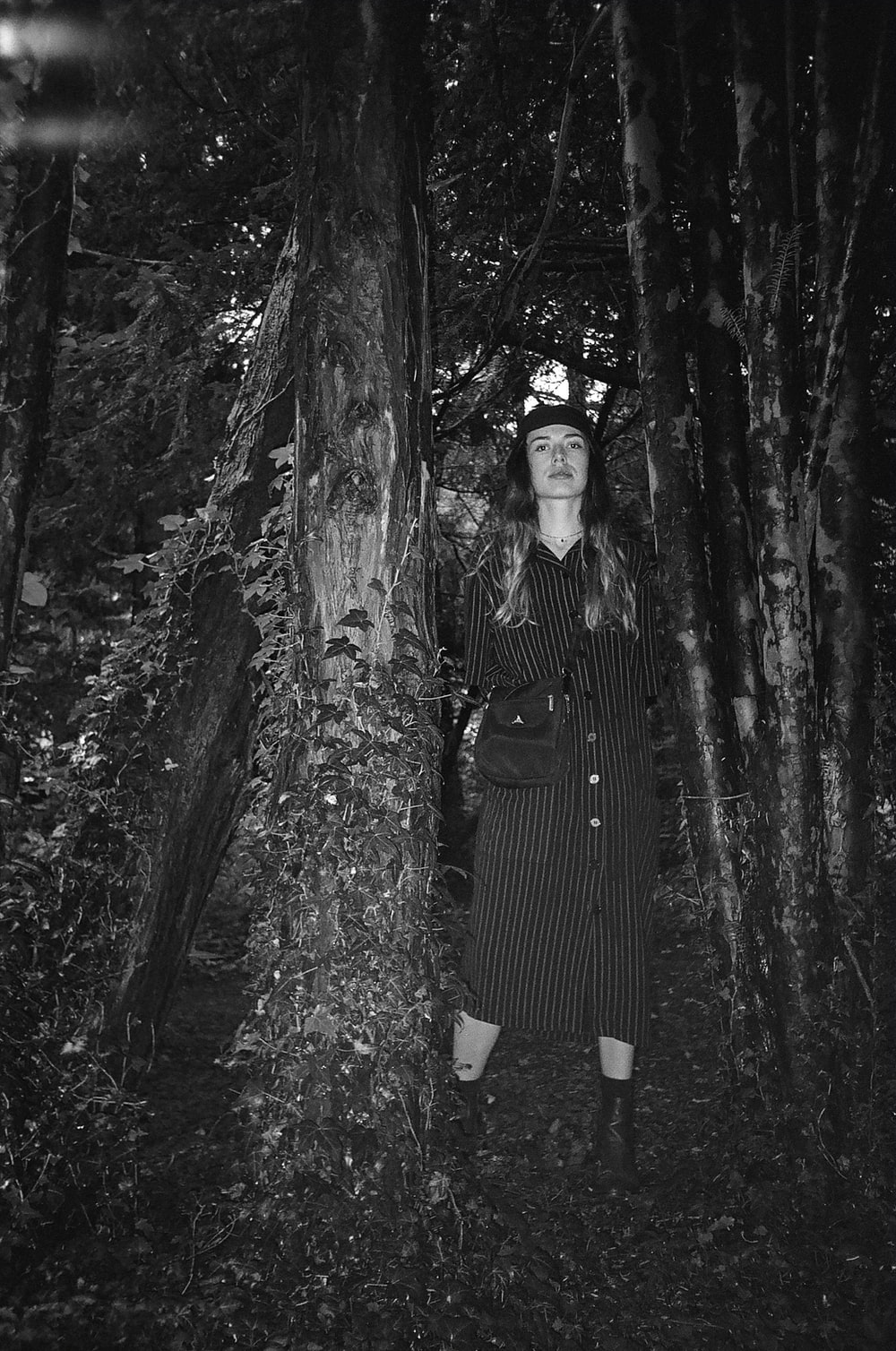 grayscale photo of woman in stripe dress standing in front of tree