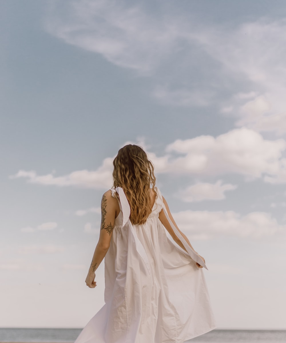 woman in white dress standing on white sand during daytime