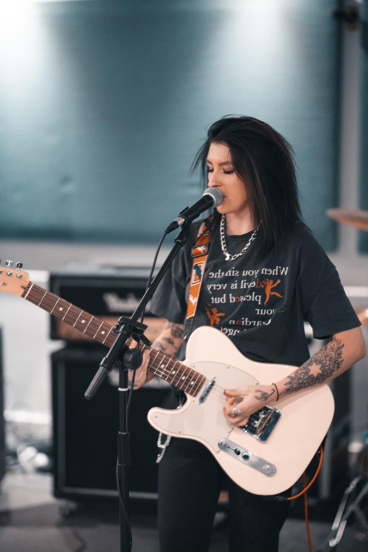 woman in black t-shirt playing electric guitar
