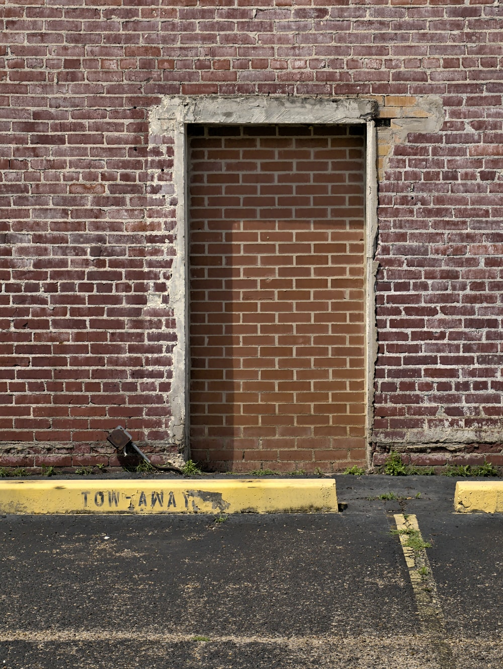 brown brick wall with black and yellow caution sign