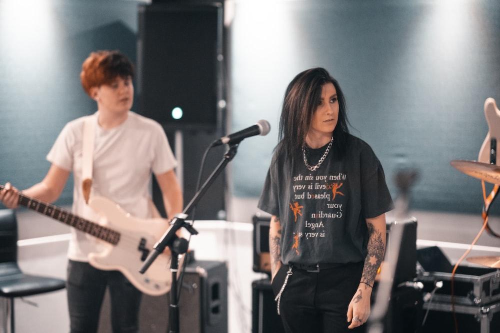 man in white crew neck t-shirt playing guitar beside woman in black long sleeve shirt