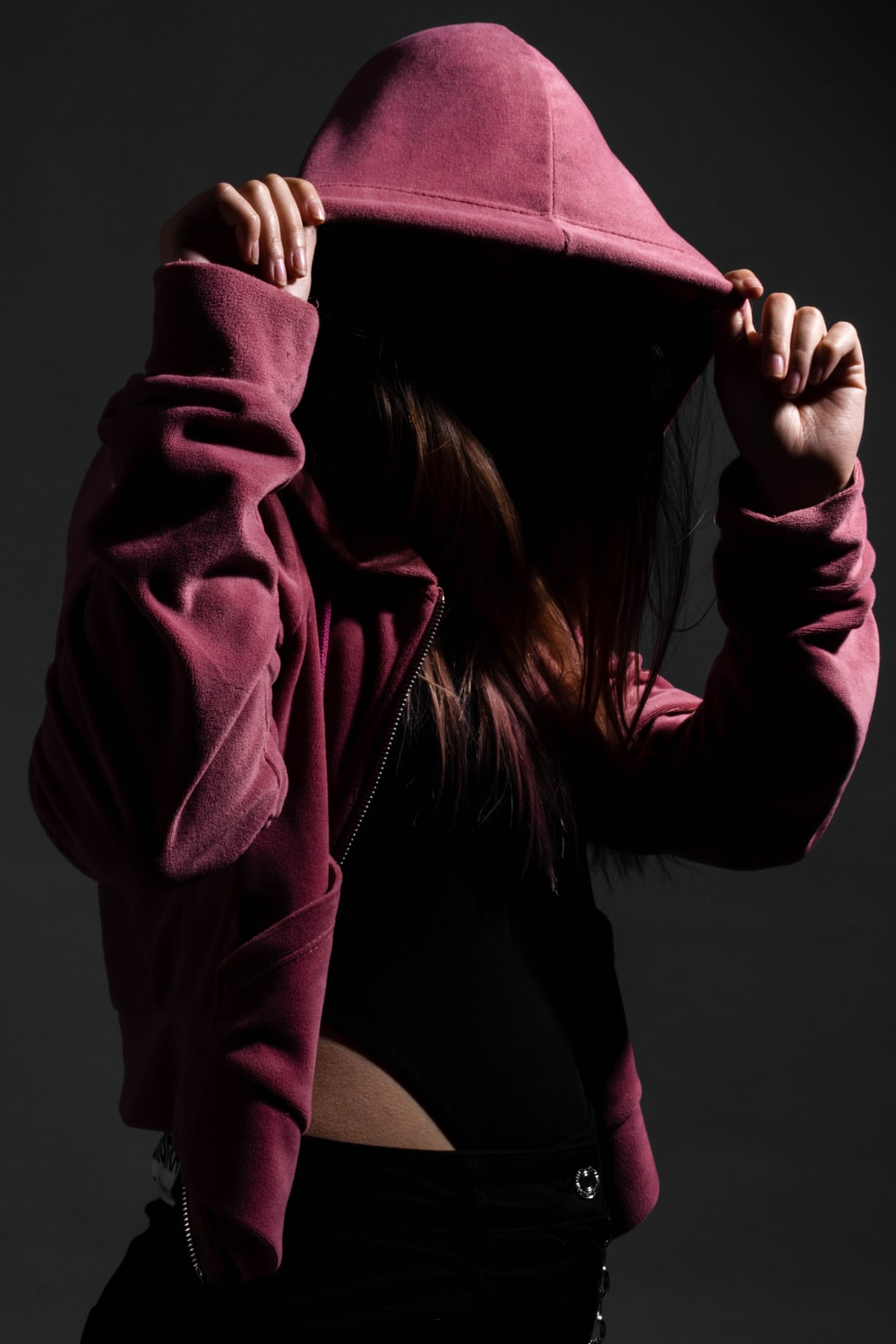 woman in pink hoodie covering her face with her hands