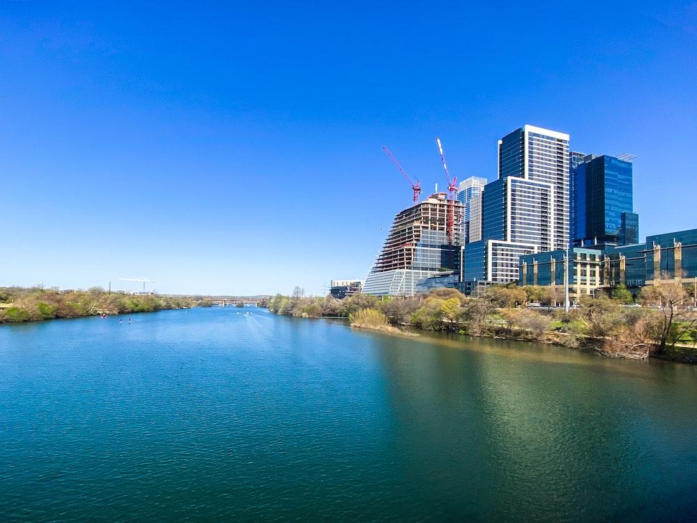 city skyline near body of water under blue sky during daytime