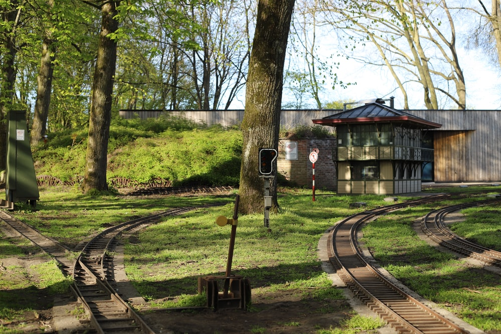 brown wooden house near trees and train rail during daytime