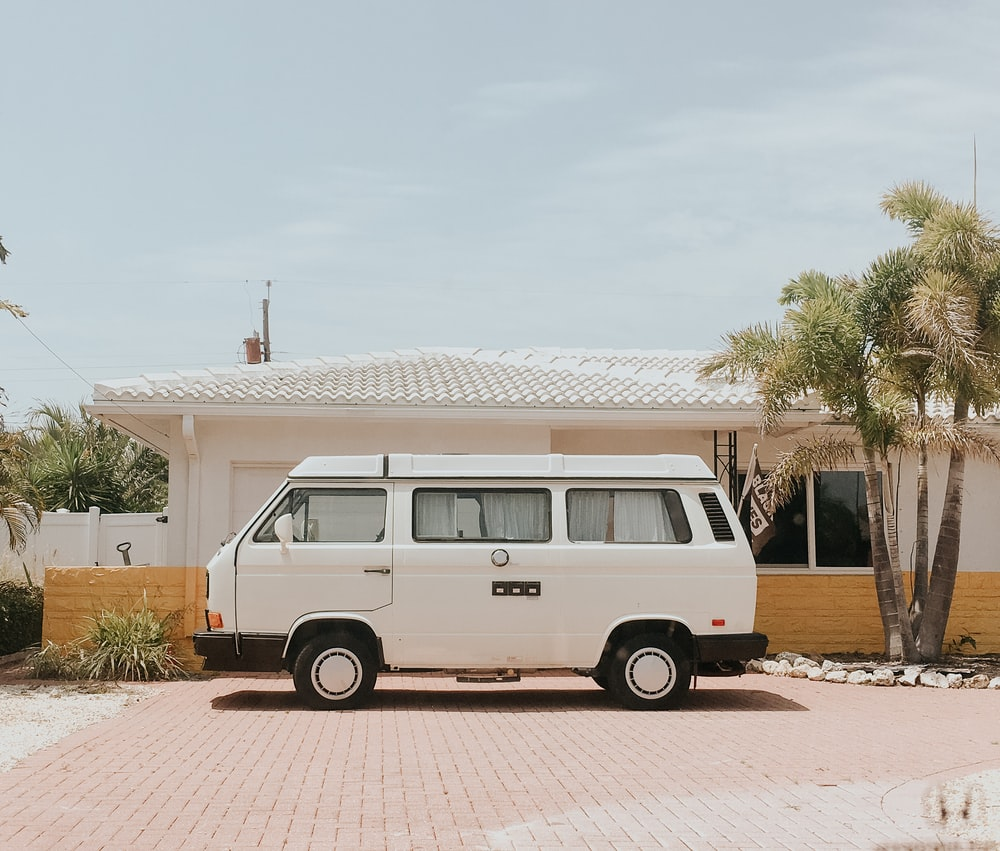 white van parked beside white and brown house