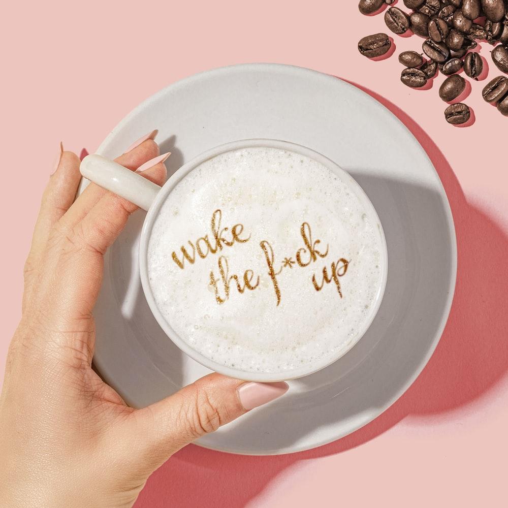 white ceramic mug with coffee beans
