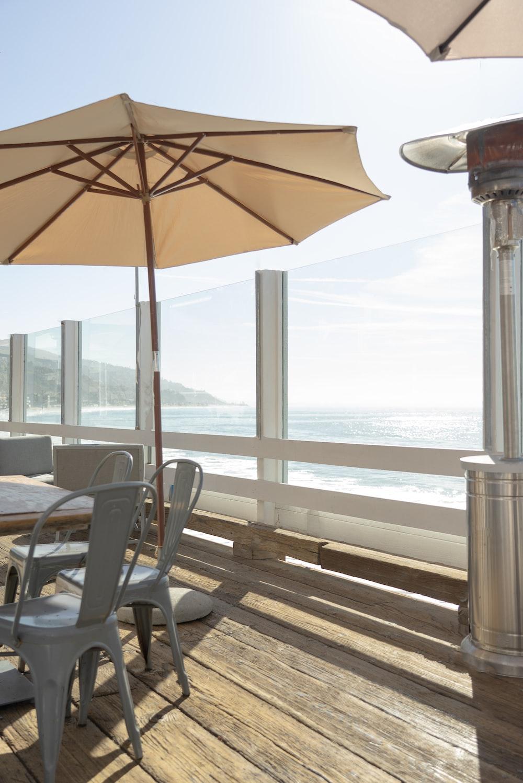 brown patio umbrella near black wooden armchair