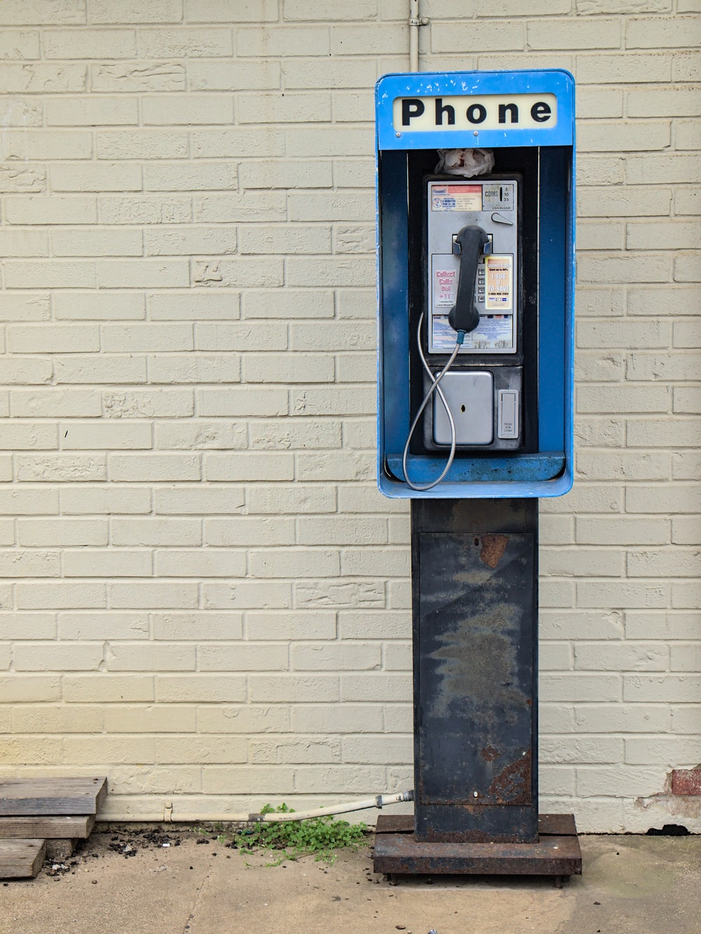 blue telephone booth mounted on white brick wall