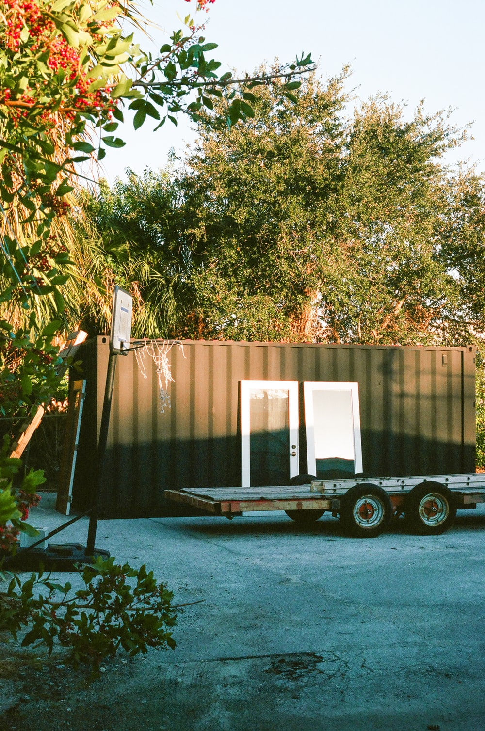 brown and black trailer near green trees during daytime