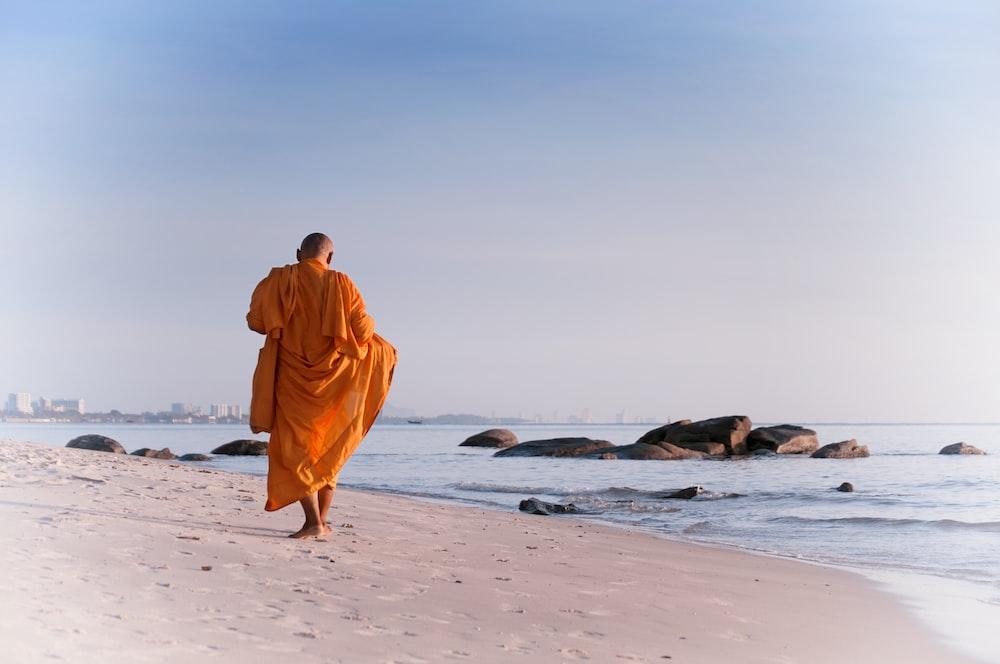 man in orange robe walking on beach during daytime