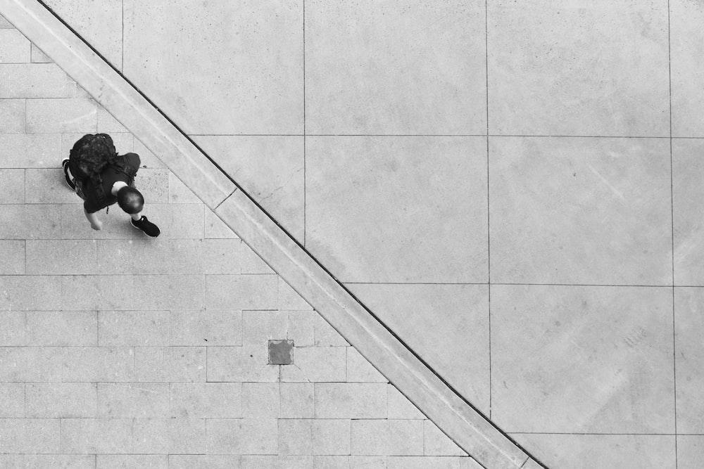 person walking on white concrete pavement