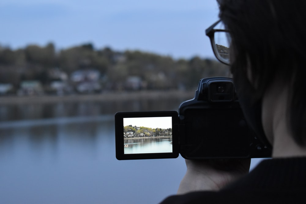 person holding black smartphone taking photo of body of water during daytime
