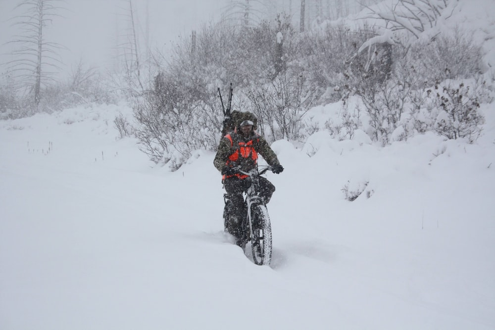 man in black jacket riding on black motorcycle on snow covered ground during daytime