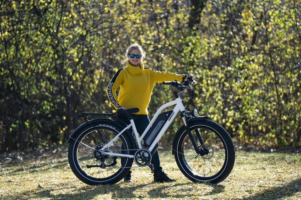 man in yellow hoodie riding white and black bicycle