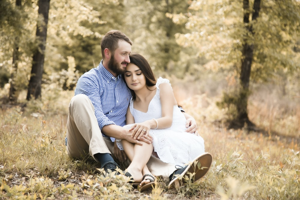 man and woman sitting on ground covered with dried leaves during daytime