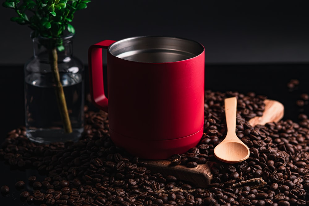 red and silver mug on brown wooden spoon