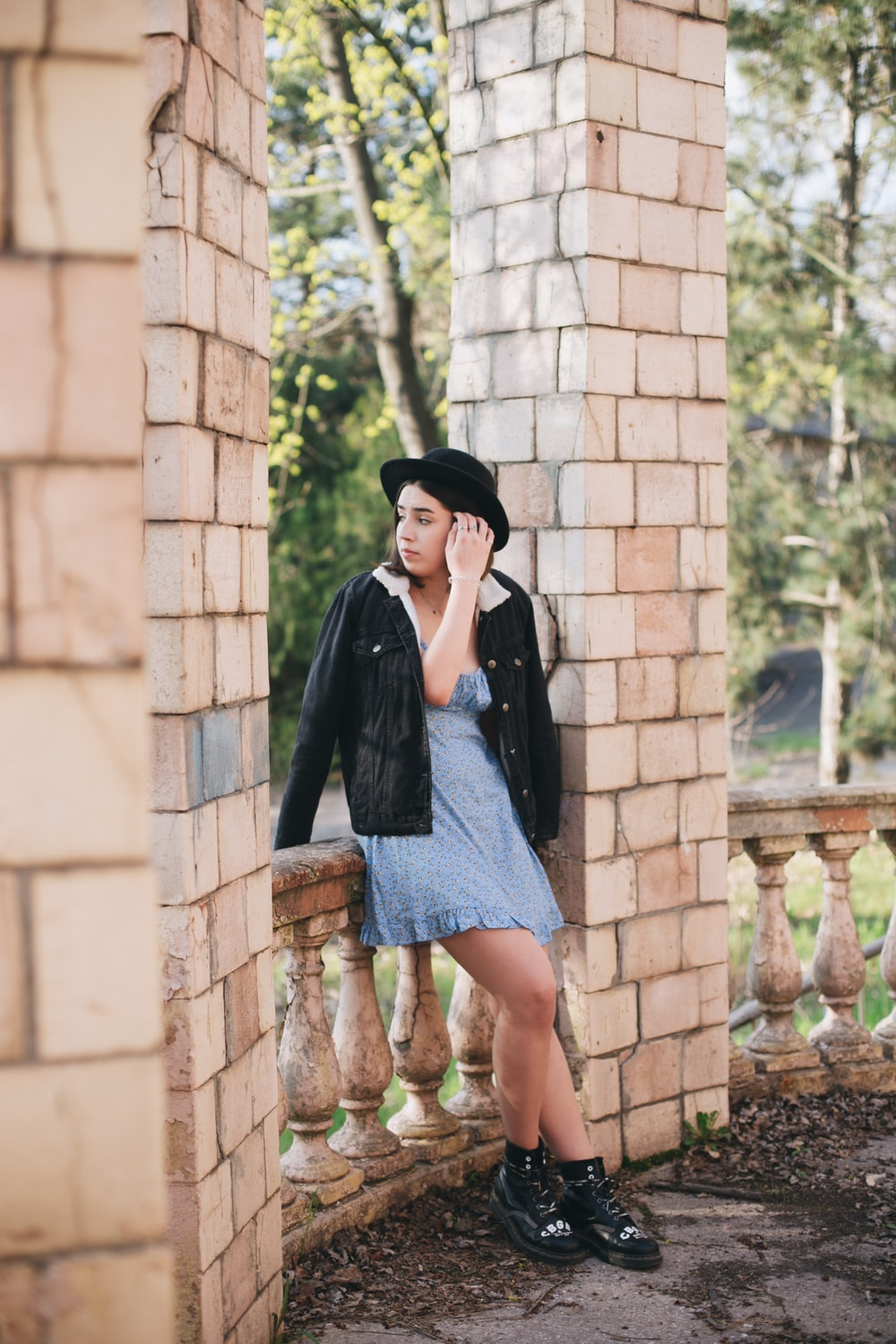 woman in black coat and blue denim skirt standing beside brown brick wall during daytime