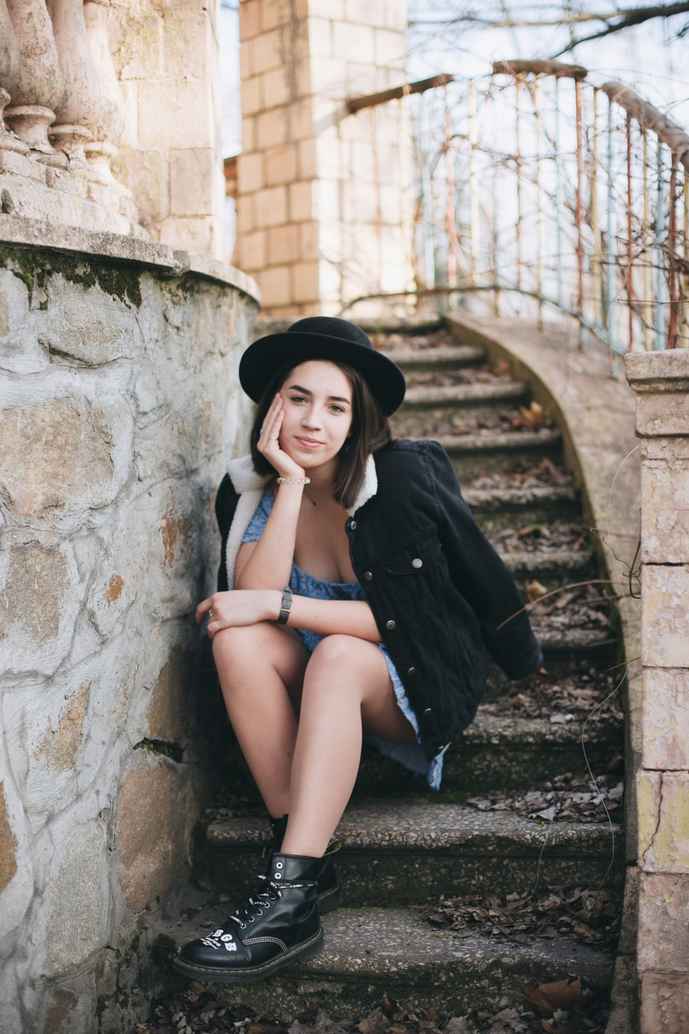 woman in black coat sitting on concrete stairs