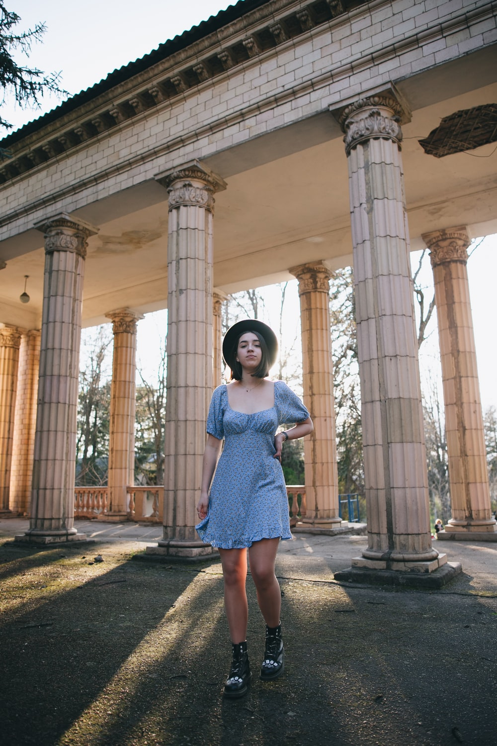 woman in blue dress standing in front of brown concrete pillar during daytime