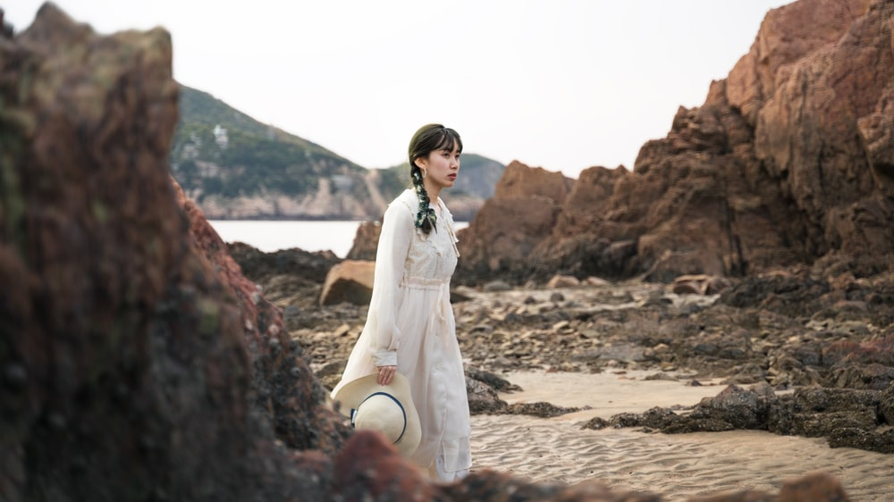 woman in white long sleeve dress standing on brown sand during daytime