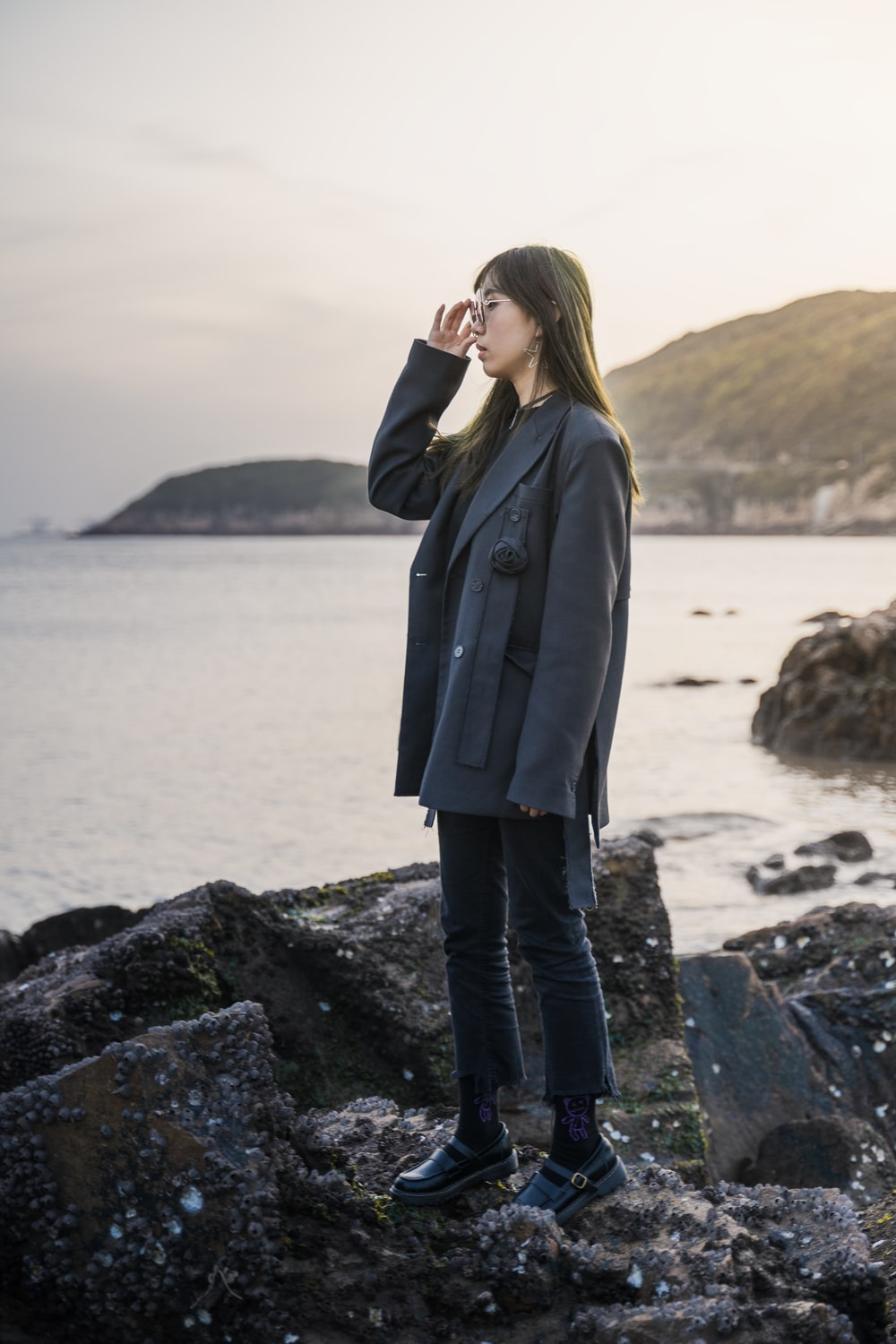 woman in black coat standing on rock formation near body of water during daytime