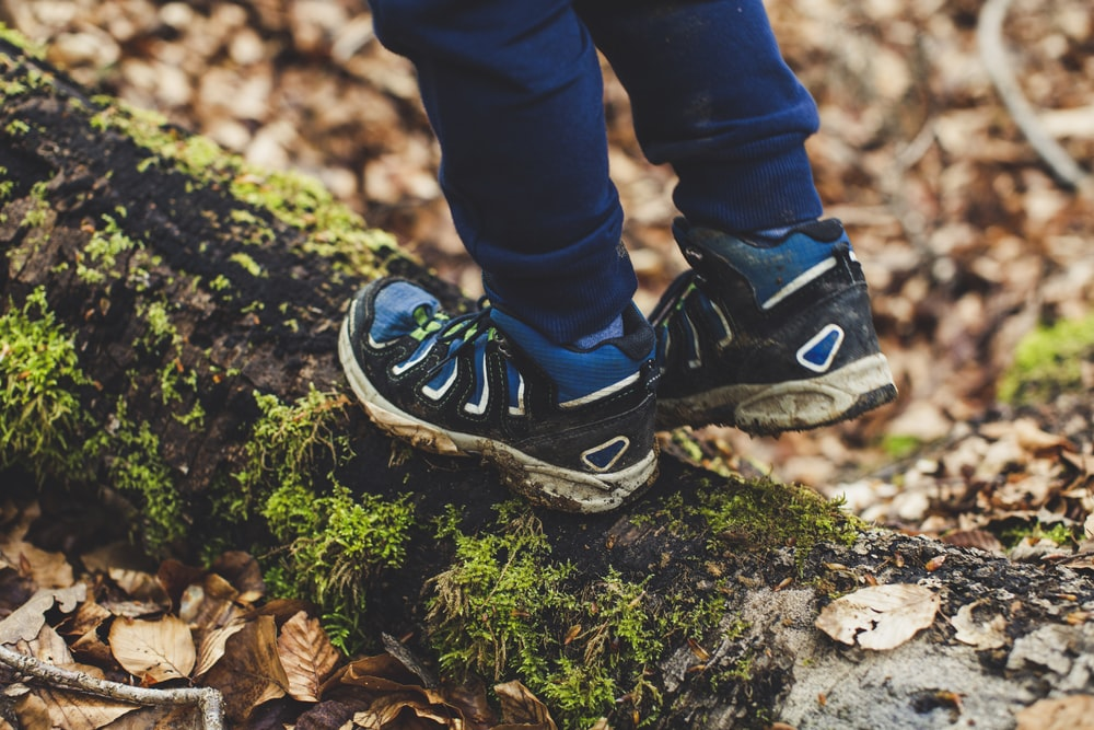 person in blue denim jeans and black and white nike sneakers standing on green moss