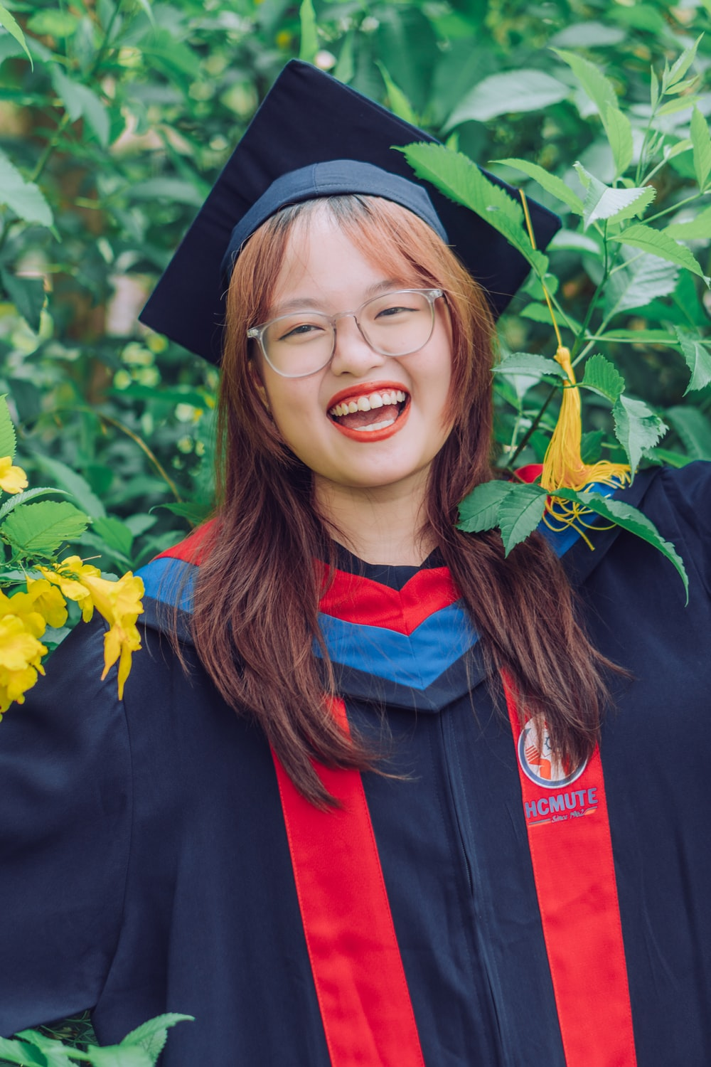smiling woman in black academic dress and red scarf