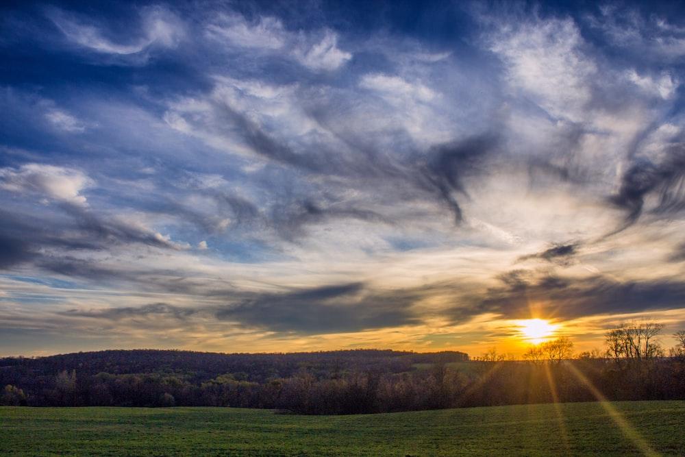 green grass field under cloudy sky during sunset