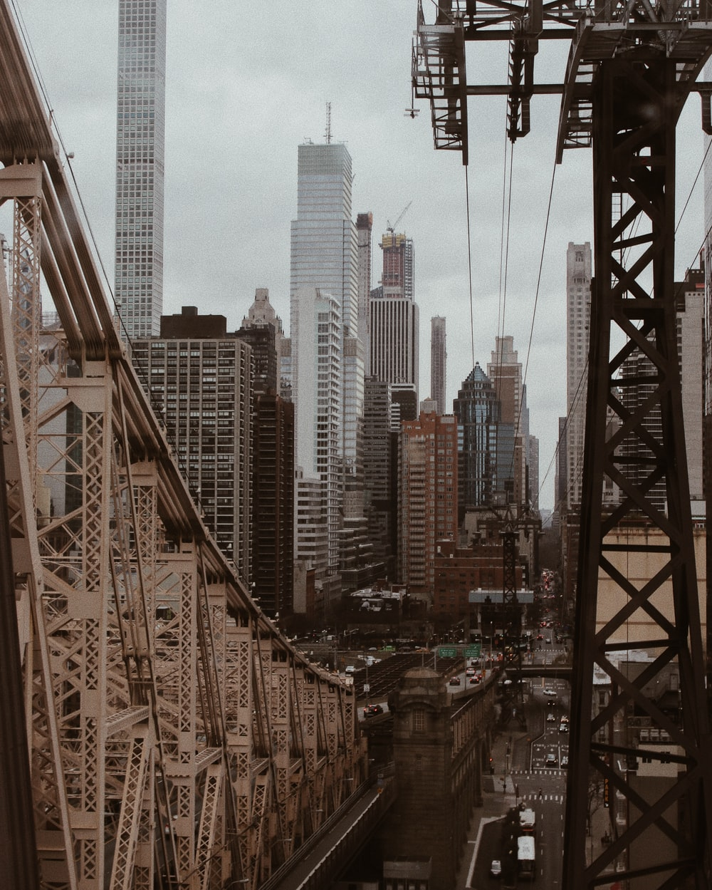 cars on bridge near high rise buildings during daytime