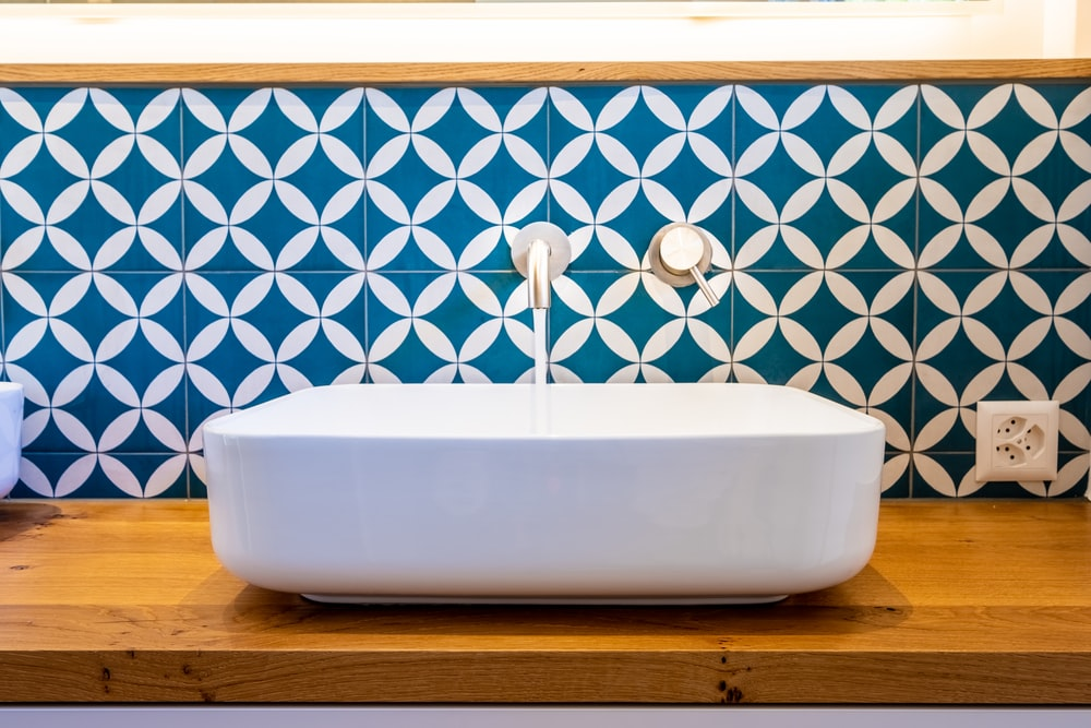 white ceramic bathtub with blue and white wall tiles