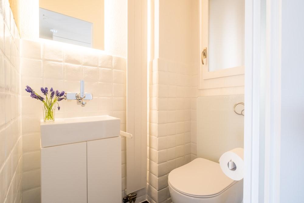 white ceramic toilet bowl beside white ceramic sink