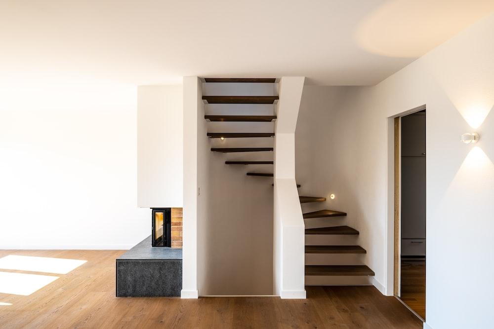 white wooden staircase near white wall