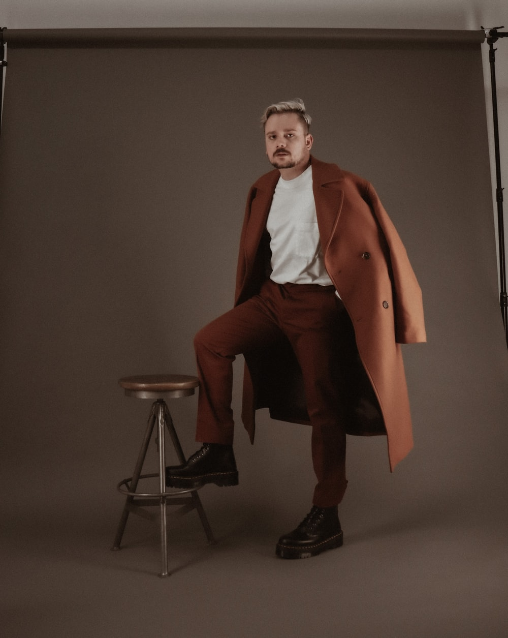 man in brown coat and black pants sitting on chair