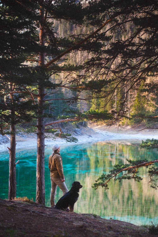 man in black jacket standing beside river during daytime