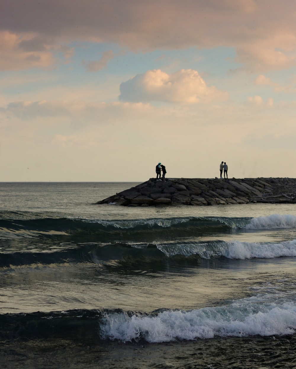 2 person standing on rock formation near sea during daytime