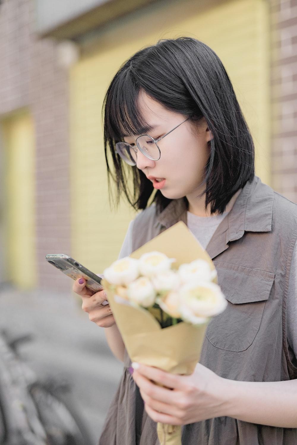 woman in gray blazer holding smartphone
