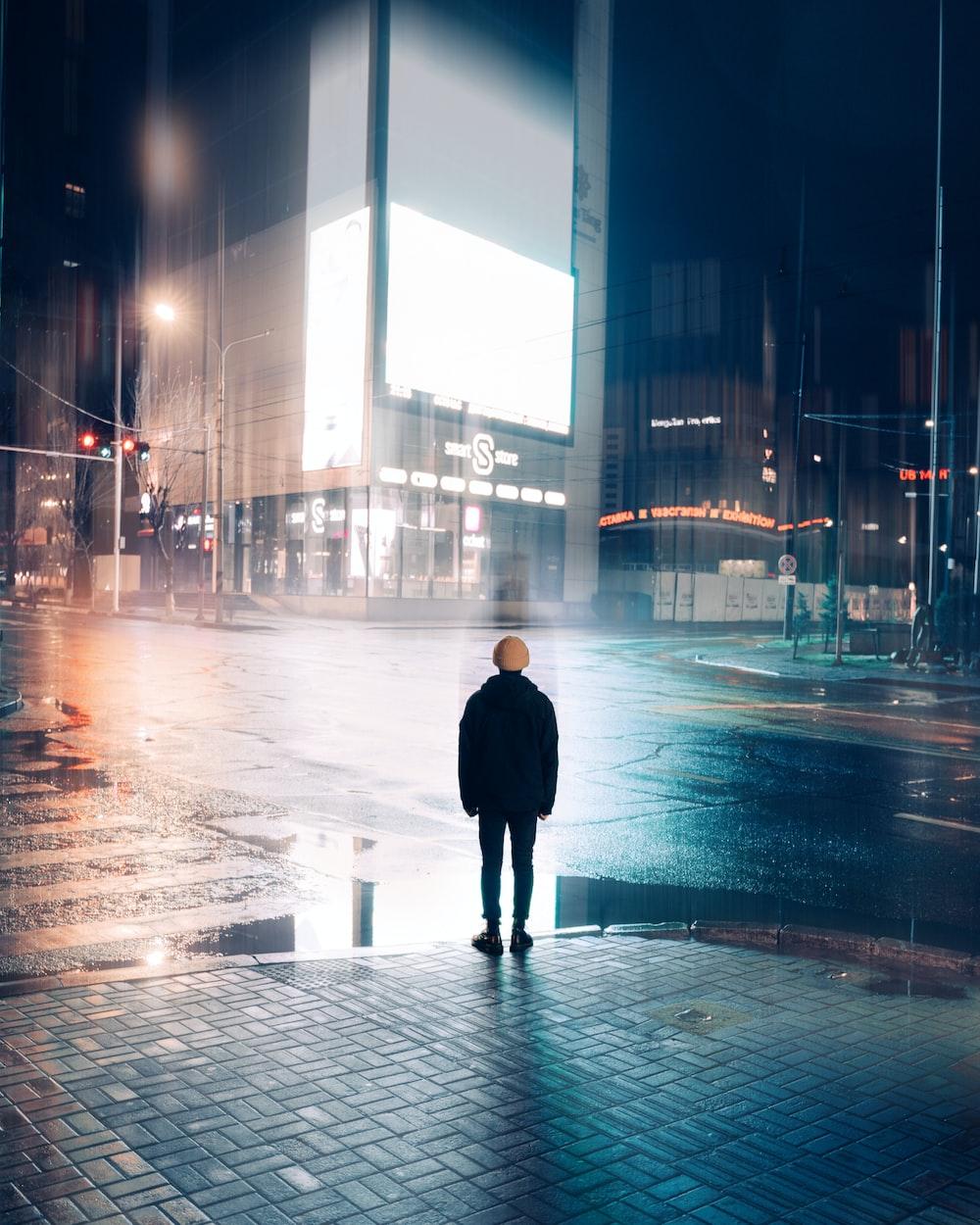 man in black coat walking on street during night time
