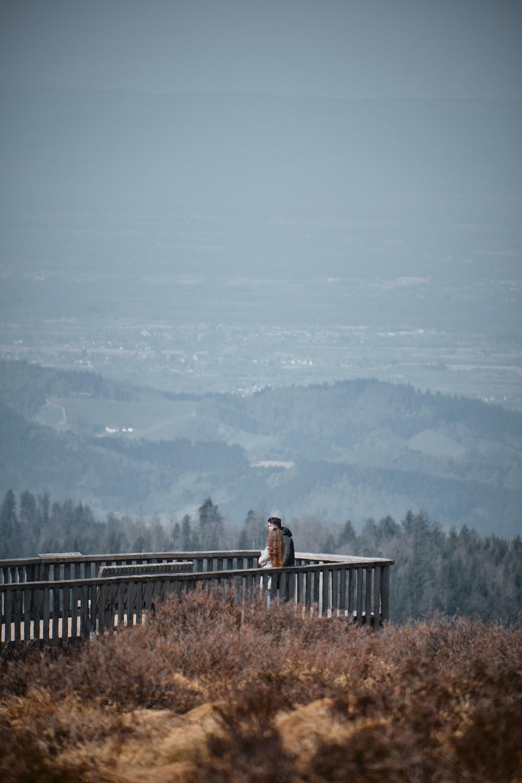woman in black jacket standing on brown wooden bridge during daytime