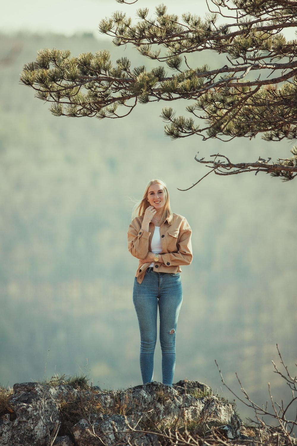 woman in pink long sleeve shirt and blue denim jeans standing on tree branch during daytime