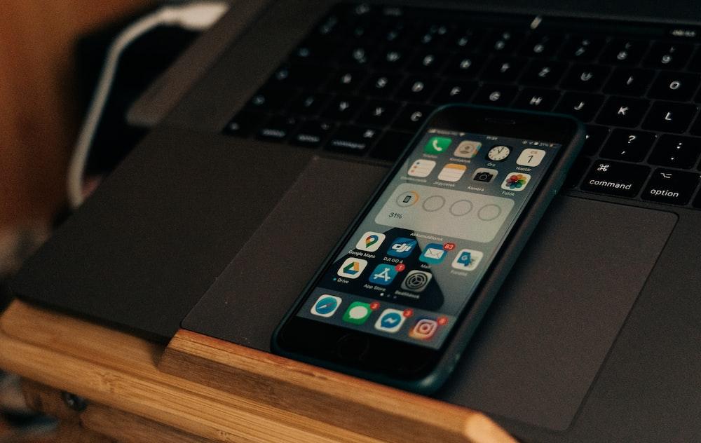 black iphone 4 on black laptop computer