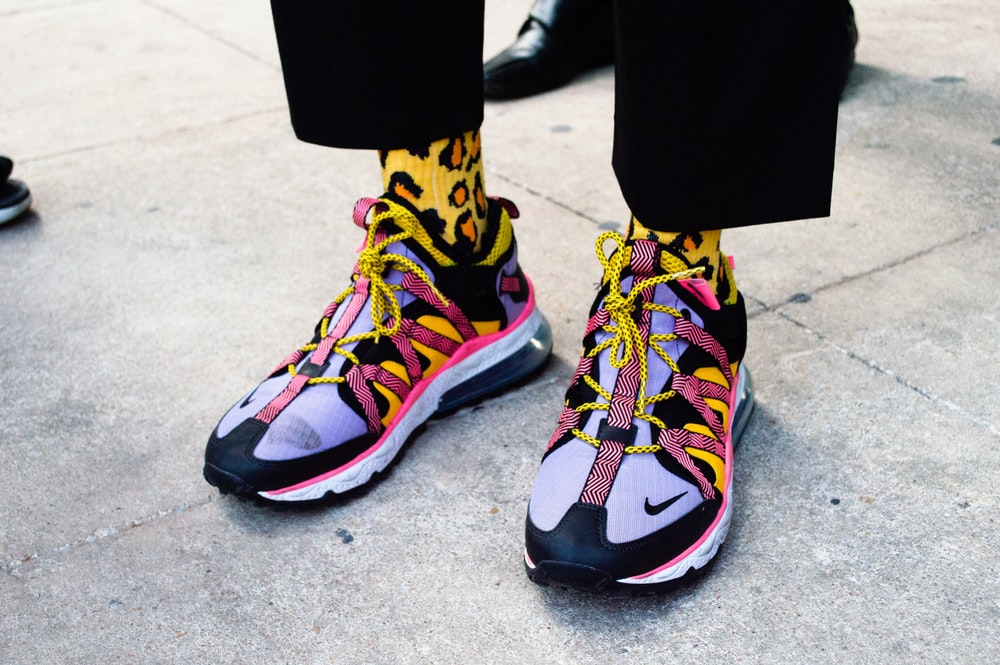 person wearing black blue and yellow nike sneakers